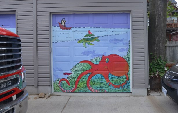 marine scene street art on a garage door in a lane, a red octopus, a green turtle swimming and a ship in the distance
