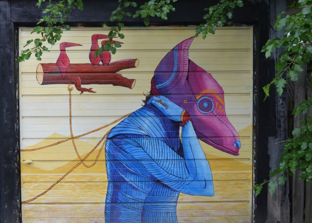 part of a mural on a garage door in a laneway, a purple headed animal creature wearing a blue top and holding onto strings attached to floating logs with little red birds on them.