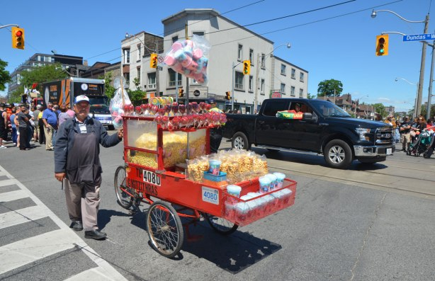 A man pushes a cart from which he is selling popcorn, candy apples and cotton candy to people watching a parade. A black truck is behind him with a boy in the passenger side who is hold a banner out the window that says Portugal on it.