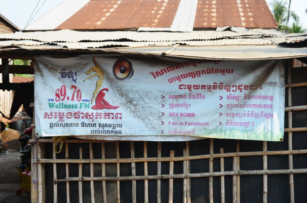 a banner outside a rough wood building, an ad for a Cambodian radio station 89.70, Wellness FM,