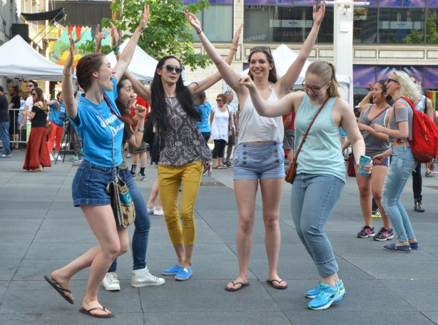people dancing at Yonge Dundas Square as a group, part of an event called Sharing Dance - 5 young women with the arms in the air