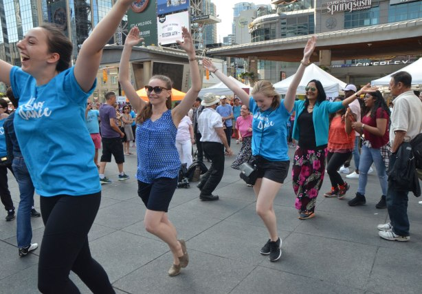 people dancing at Yonge Dundas Square as a group, part of an event called Sharing Dance