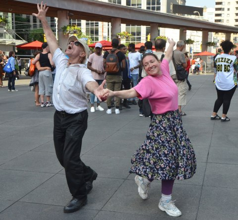 people dancing at Yonge Dundas Square as a group, part of an event called Sharing Dance - a couple dancing together