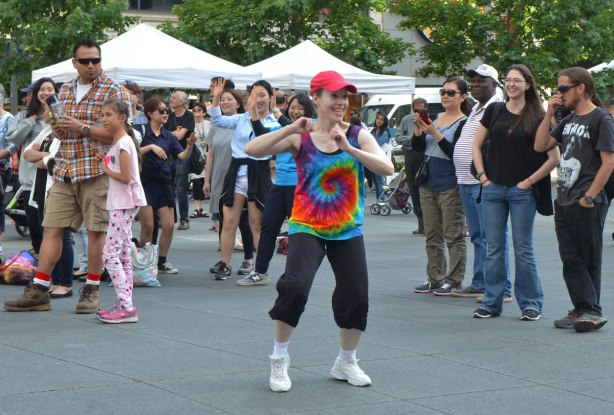 people dancing at Yonge Dundas Square as a group, part of an event called Sharing Dance - a woman in a tie dyed T-shirt and orange cap dances on her own while others watch