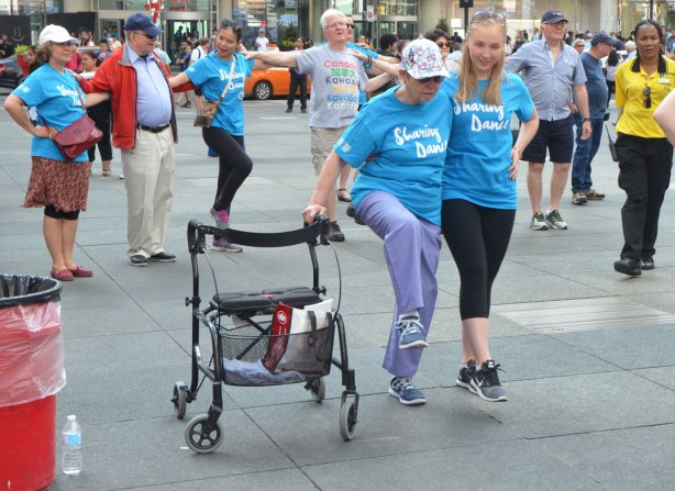 people dancing at Yonge Dundas Square as a group, part of an event called Sharing Dance - a younger woman helps an older woman with a walker to lift her knees in ballet moves