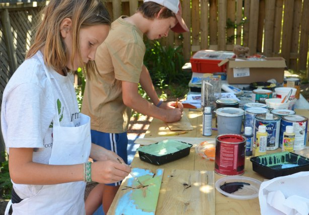 kids painting designs on wooden shingles, outdoors.
