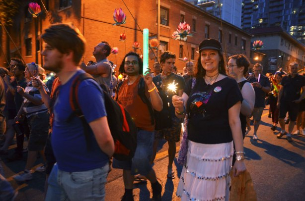 people walking in a night time parade for nuit rose, down Church St., one man is holding up a light stick, a woman is holding a sparkler, other people have lanterns and glow sticks.