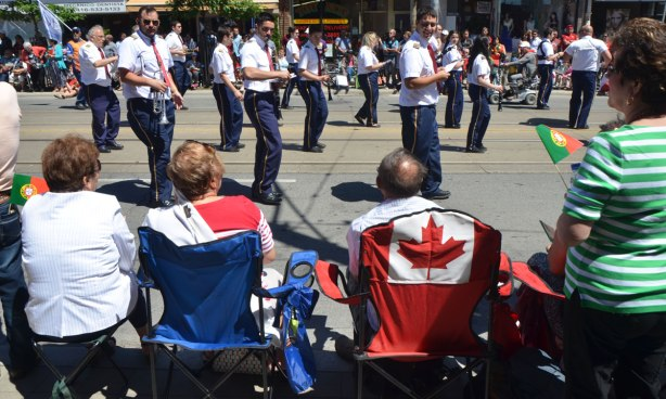 Spectators at a parade, sitting on chairs, one of which has a Canadian flag on the back. Passing by is a marching band in dark pants and white shirts. Portugal Day parade on Dundas West.