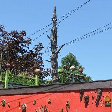 a tall sculpture resembling a spinal column rises above a garage in a lane. constructed of bits of wood and found objects.