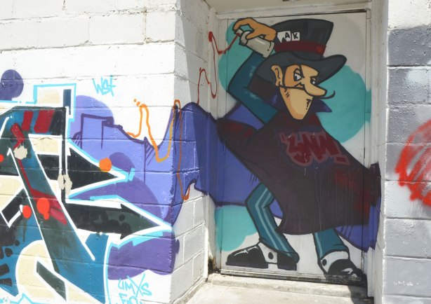 street art painting on a doorway and wall in an alley, of cartoon character Dastardly Whiplash with his mustache, black cape and top hat spray painting a tag on a wall.