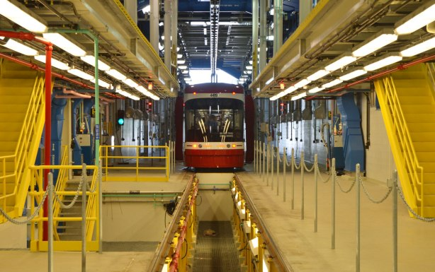 the back of a new streetcar as it passes through interior of Leslie Barns streetcar facility, a large, tall interior space with lots of pipes