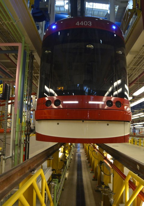 A streetcar sits in a repair bay of the Leslie Barns, space underneath the streetcar for workers to go down and work on the underside of the streetcar.