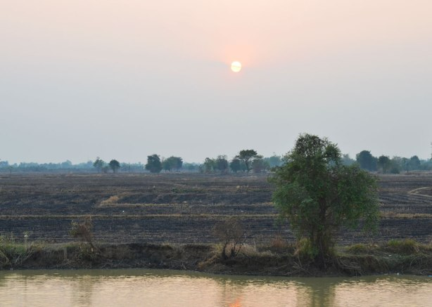 sunset over the Cambodian countryside, river in the foreground, dirt fields and a few trees in the background.