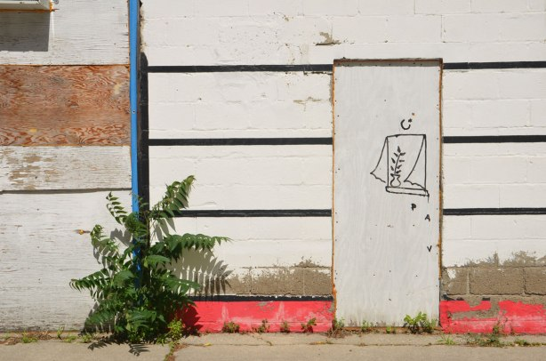 white door on white wall. Someone has drawn a window on the door with a plant in the window. Bottom of wall is red, three black horizontal stripes on the wall, one vertical blue pipe on the left side