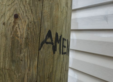close up of a wood pole beside a white garage. Written in capital letters, black ink, is the word Amen