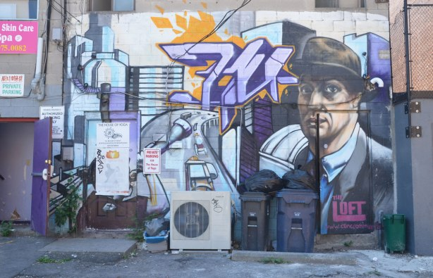 back of a row of stores, lane view, air conditioning unit, garbage bins, a mural of a man wearing a suit and hat. Sign on mural says The Loft, by