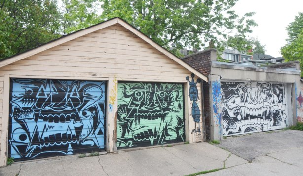 three garages in a row in an alley, all painted with a large monster face