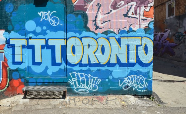 Street art painting in a n alley that says Toronto in blue