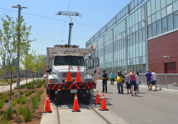 a special TTC truck sits outside Leslie Barns TTC facility on Doors Open day, the truck is designed to run on streetcar tracks and is used to repair tracks and wires. There are people looking at the truck