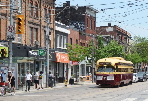 An old restored TTC streetcar, maroon and yellow, on Queen St. East
