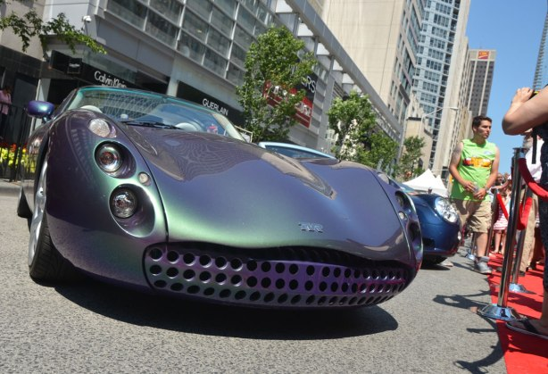 a purplish green shiny sports car, a Tuscan, by TVR motors, parked on Bloor St. for the Yorkville exotic car show.