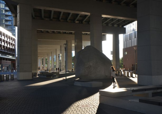 evening, low angle sunlight shines under the Gardiner Expressway where it has been developed with paving stones and some large rocks.