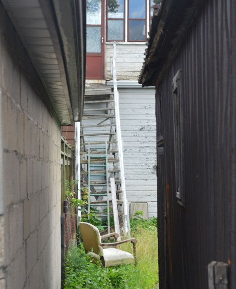 looking through the gap between two garages in a lane, into a backyard with a chair on the lawn, and a ladder and steps that look like a ladder up to a door at the second storey level