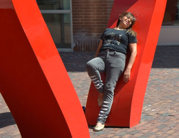 A woman is posing by the large red heart in the distillery district, she is leaning back on one side of it.
