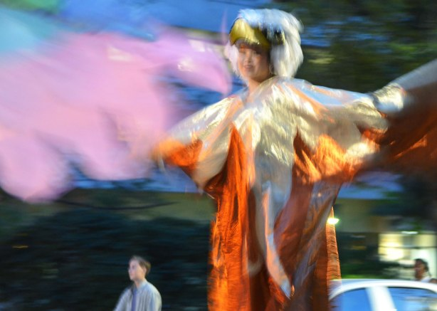 A woman in a flowing costume with eagle head, up on stilts, in a night time parade for nuit rose