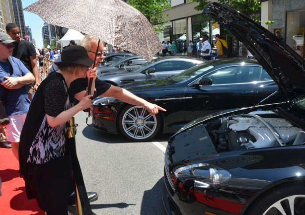 a man with grey hair and black glasses is pointing to the front of a black sports car with its hood up. He is pointing out something to the woman beside him who is dressed in black with black hat and holding an umbrella over her head. They are behind a barrier at an outdoor exotic car show