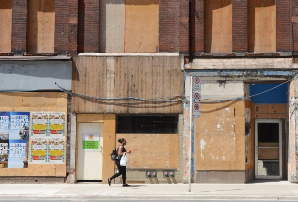 a woman walks on a sidewalk on Yonge St past old brick buildings with their doors and windows boarded up
