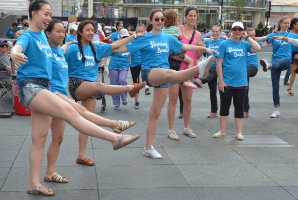 people dancing at Yonge Dundas Square as a group, part of an event called Sharing Dance - young women in blue t-shirts, arms linked, kicking