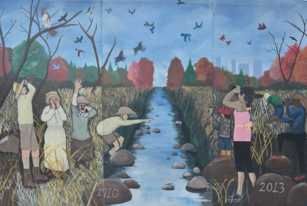 1910 to 2013, mural of past and present along the creek. Kids playing on either side, the past on the left, the present on the right, bird watching, standing in the grass,