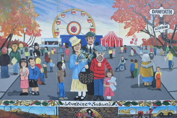 mural depicting people at a fair. A child is licking a giant round lollipop, a girl is holding a doll, a ferris wheel is in the background.