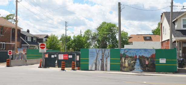 Looking across a street to a construction site around which a fence has been erected. There are three murals painted on the hoardings.