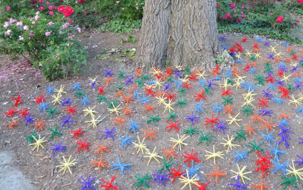 under a tree in a park, with roses in the background, many coloured 3D stick shapes that have been covered with yarn, lie on the ground.