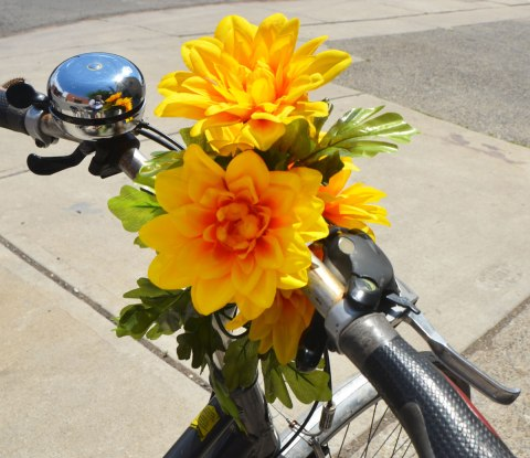 two large yellow flowers attached to the handle bars of a bicycle