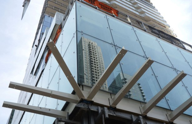 part of a glass wall of windows of a tall condo under construction - reflections in the windows, looking up from the ground floor, the supports of an overhang at the first floor can be seen but the overhang itself is not finished