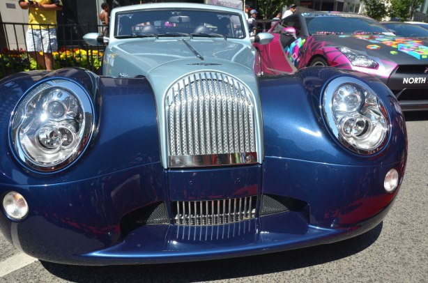 front end of a two toned blue Morgan car in a car show outside on Bloor Stree, with a rally car in different colours beside it.