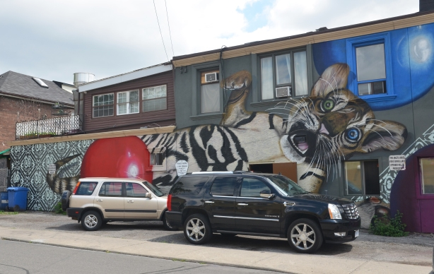 large mural of a tiger cub playing with two balls, one red and one blue. The cub has one green eye and one blue eye. Covers the whole of the side of a building