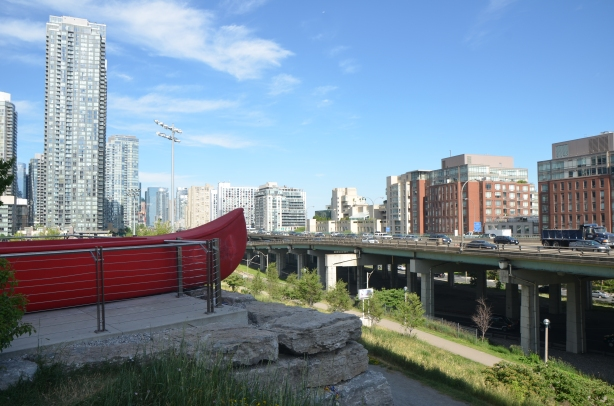 The end of a large red canoe, an artwork by Douglas Coupland called 'Tom Thomson's Canoe' sits in a park, high above the surrounding scenery. Looking southwest towards the elevated Gardiner Expressway and the condo developments south of it.