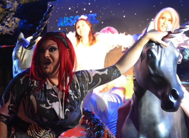two people sitting on unicorns to have their picture taken with a person in a red wig hamming it up in front of them, nuit rose, night time.