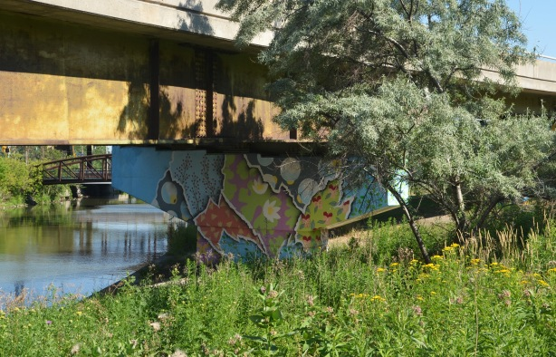 a bent supporting an offramp has been covered in a bright mural, grass and weeds grow in front, the river is behind, a small tree also in the picture