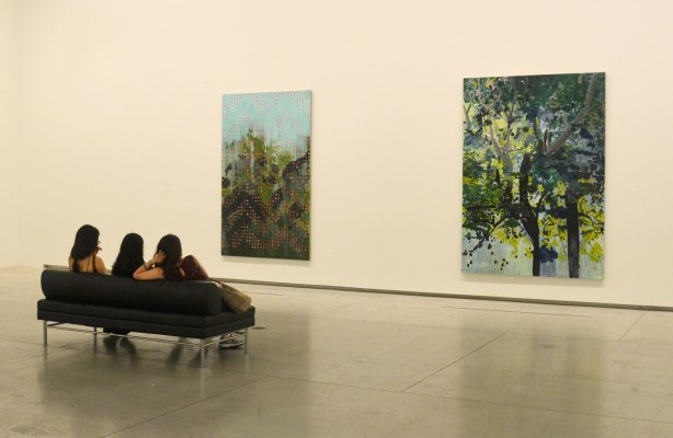 three young women sitting on a couch with their backs to the camera, they are looking at two large paintings on a wall, by Hurvin Anderson.