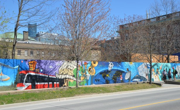 part of a mural on an artwall on hoardings around a construction site for a new engineering building at the University of Toronto, new TTC streetcar in the mural as well as some musicians, an astronaut floating in space
