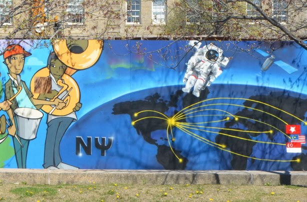 part of a mural on an artwall on hoardings around a construction site for a new engineering building at the University of Toronto, two musicians and an astronaut floating in space