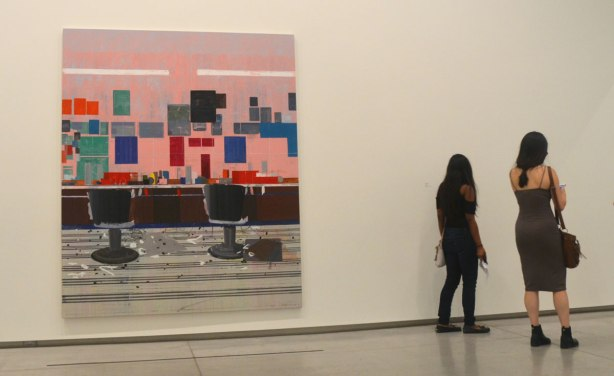 two young women walk away from a large painting hanging on an art gallerywall.  two barber chairs in a barber shop, empty.  Bright pink wall with squares of colour.