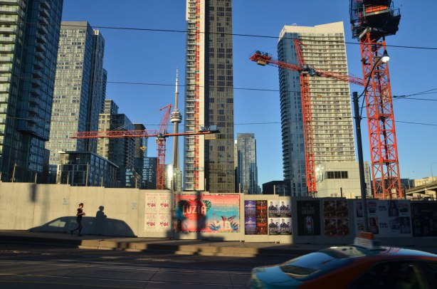 late afternoon, long shadows, yellowish tint to the photo, looking east from Bathurst, south of Front, north of the Gardiner, wood construction hoardings with posters on it, many orange cranes, some condos already built, a woman jogging past, cars on the street.