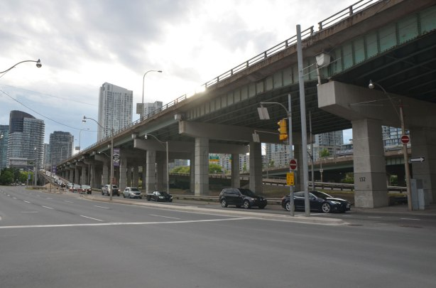 major road with traffic under an elevated expressway in a city, long ramp from the upper level to the lower. Gardiner Expressway and Lakeshore Blvd in Toronto, at Spadina looking west