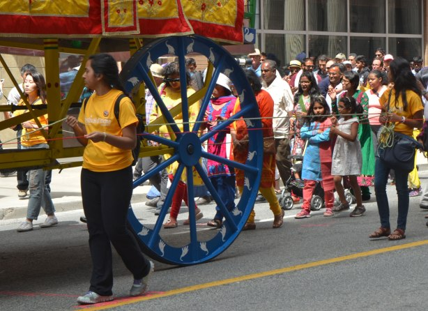 a large blue wheel that is holding up a chariot float in the Festival of India parade, people walking beside and behind it as they walk down Yonge Street